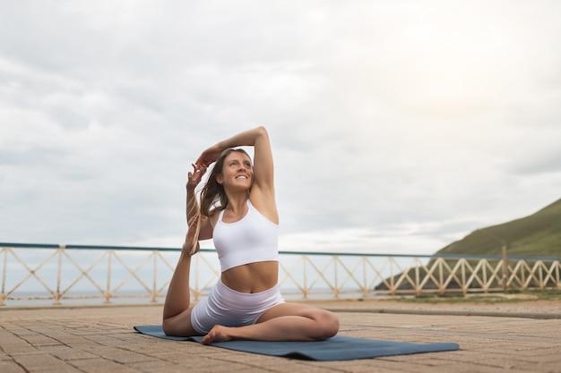Blond kaukaska kobieta robi joga na świeżym powietrzu z białą odzieżą sportową na zachmurzone niebo