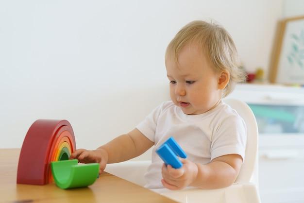 Blond kaukaski maluch bawi się drewnianymi zabawkami edukacja dziecka w domu pozioma kopia przestrzeń