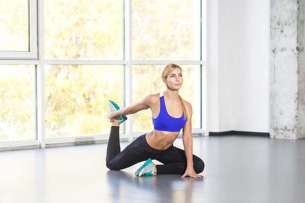 Blond kobieta aktywności w postawie jogi król gołąb z jedną nogą