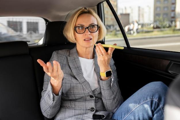 Blond kobieta biznesu rozmawia przez telefon w swoim samochodzie