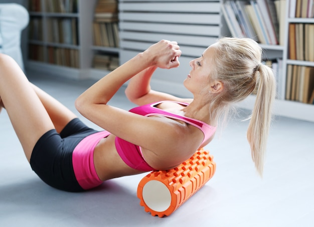 Blond kobieta ćwiczenia treningowe z wałkiem piankowym