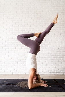 Blond kobieta ćwiczy jogę w domu, stojąc na głowie