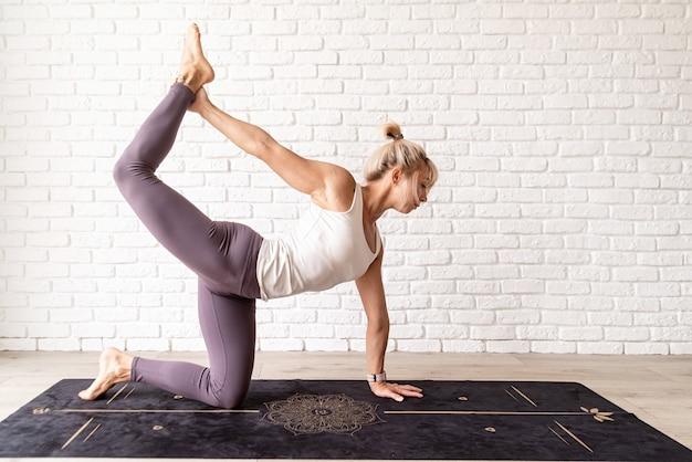 Blond kobieta ćwiczy jogę w domu