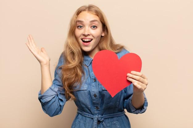 Blond kobieta czuje się szczęśliwa, podekscytowana, zaskoczona lub zszokowana, uśmiechnięta i zdumiona czymś niewiarygodnym