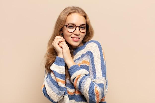 Blond kobieta czuje się zakochana i wygląda słodko, uroczo i szczęśliwie, uśmiechając się romantycznie z rękami przy twarzy