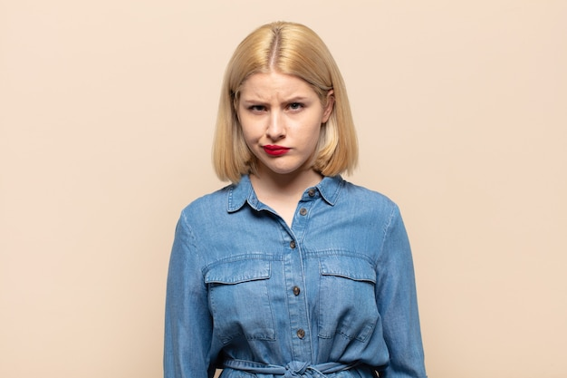 Blond kobieta czuje się zdezorientowana i wątpi, zastanawia się lub próbuje wybrać lub podjąć decyzję