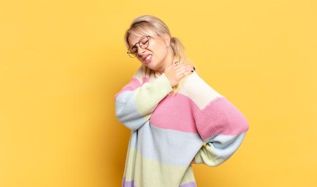 Blond kobieta czuje się zmęczona, zestresowana, niespokojna, sfrustrowana i przygnębiona, cierpi z powodu bólu pleców lub karku