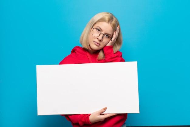 Blond kobieta czuje się znudzona, sfrustrowana i senna po męczącym, nudnym i żmudnym zadaniu, trzymając twarz dłonią