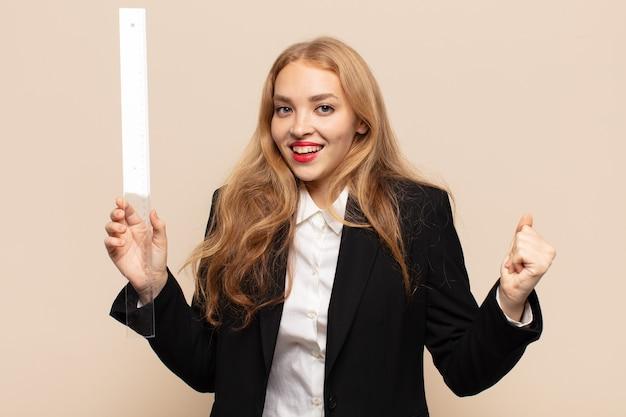 Blond kobieta czuje się zszokowana, podekscytowana i szczęśliwa, śmiejąc się i świętując sukces, mówiąc wow!