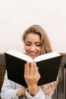 Blond kobieta czyta na zewnątrz