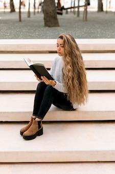 Blond kobieta czytająca na zewnątrz