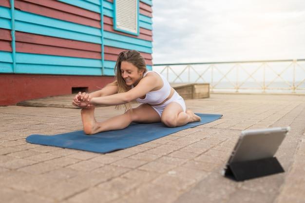 Blond kobieta dokonywanie zajęcia jogi online z białą odzież sportową. na tle czerwono-niebieskiej kabiny nad morzem