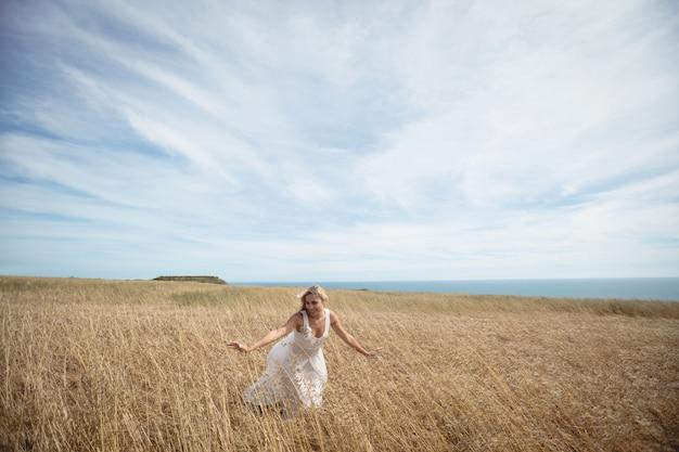 Blond kobieta dotyka uprawy w polu