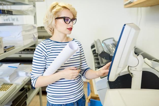 Blond kobieta działa prasa drukarska