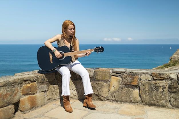 Blond kobieta grająca na czarnej gitarze akustycznej siedzi w kamiennej ścianie na tle morza w słoneczny dzień