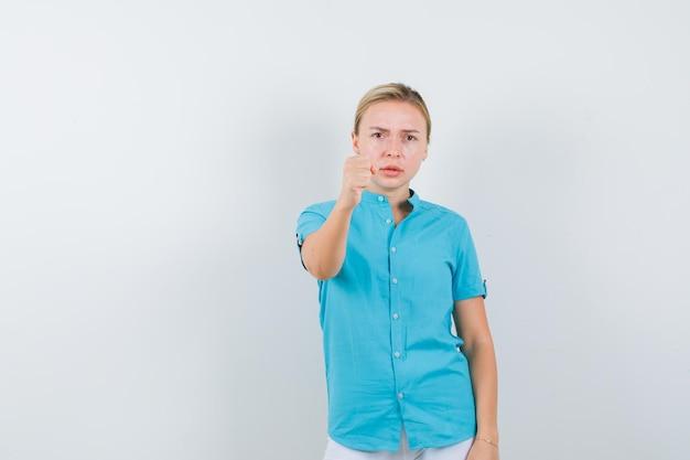 Blond kobieta grozi pięścią w niebieskiej bluzce i wygląda na surowo odizolowaną