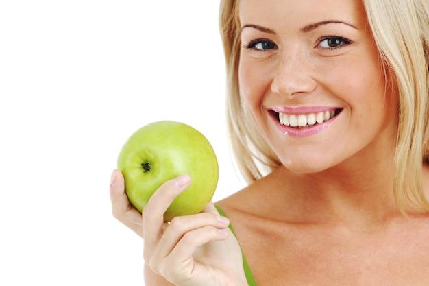 Blond kobieta je zielone jabłko na białym tle
