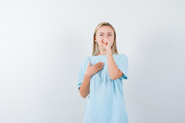 Blond kobieta kaszle, trzyma pięść na ustach w niebieskiej koszulce i wygląda na wyczerpaną