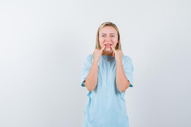 Blond kobieta kładzie palce wskazujące na ustach w niebieskiej koszulce i wygląda uroczo