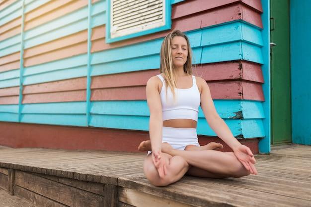 Blond kobieta medytuje przed niebiesko-czerwoną drewnianą kabiną