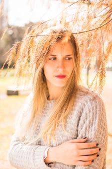 Blond kobieta model patrzeje na boku pod drzewną koroną