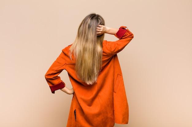 Blond kobieta myśli lub wątpi, drapie się po głowie, czuje się zdziwiona i zdezorientowana, widok z tyłu lub z tyłu