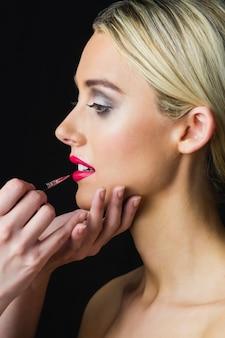 Blond kobieta o jej usta wykonane przez charakteryzator