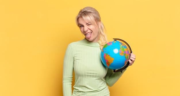 Blond kobieta o pogodnym, beztroskim, buntowniczym nastawieniu, żartuje i wystawia język, dobrze się bawi