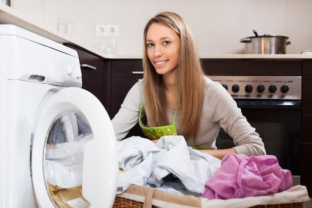 Blond kobieta oddanie ubrania do pralki