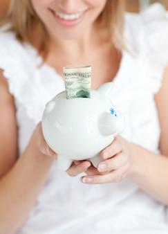Blond kobieta oszczędzania pieniędzy w piggy-bank