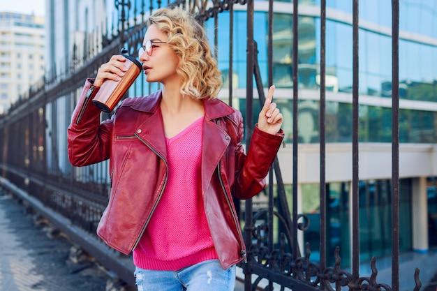 Blond kobieta pozuje na nowoczesnych ulicach, pije kawę lub cappuccino. stylowy jesienny strój, skórzana kurtka i dzianinowy sweter. różowe okulary przeciwsłoneczne.
