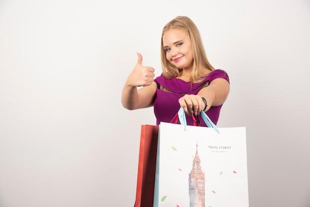 Blond kobieta robi aprobatom z torby na zakupy.