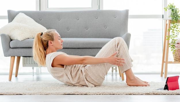 Blond kobieta robi ćwiczenia jogi abs online z lekcją wideo na tablecie