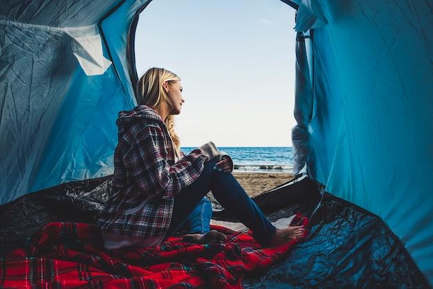 Blond kobieta siedzi na namiocie i patrzy na morze