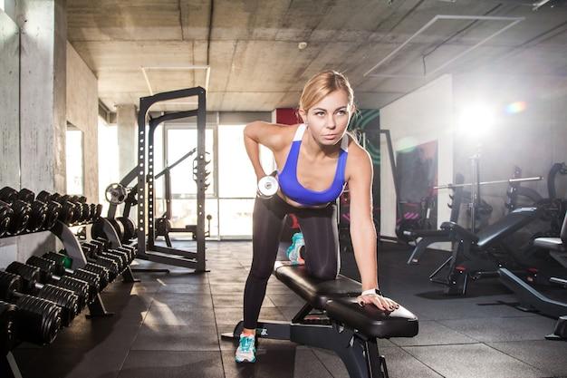 Blond kobieta sportowa pompki hantle