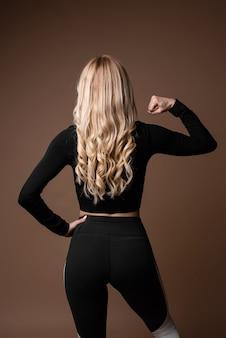 Blond kobieta sportowy z szczupłą opalone ciało w czarnej odzieży sportowej pozowanie na beżowym tle. widok z tyłu