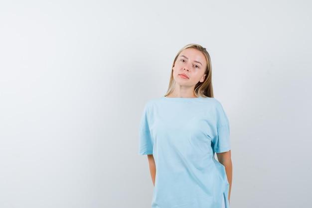 Blond kobieta stoi prosto i pozuje do kamery w niebieskiej koszulce i wygląda poważnie