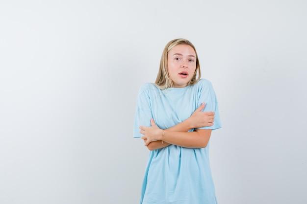 Blond kobieta stoi skrzyżowanymi rękami w niebieskiej koszulce i wygląda na zaskoczoną