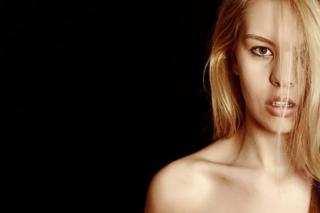 Blond kobieta stwarzających z czarnym tłem