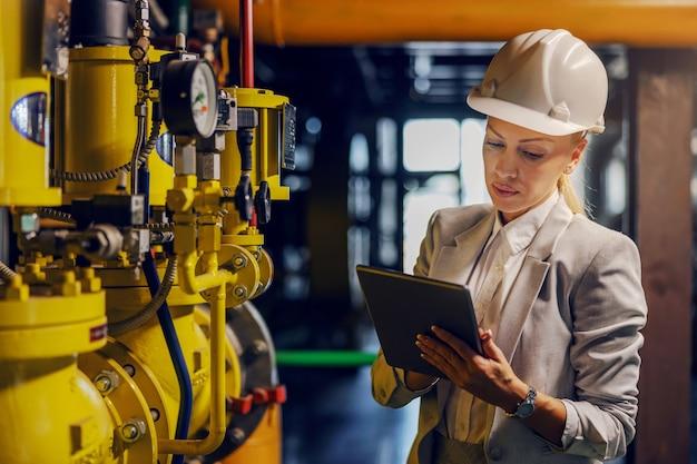 Blond kobieta sukcesu w wizytowym stroju, sprawdzająca maszyny i trzymająca tablet, stojąc w elektrowni.