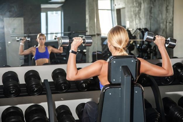Blond kobieta trenuje biceps z hantlami patrząc w lustro