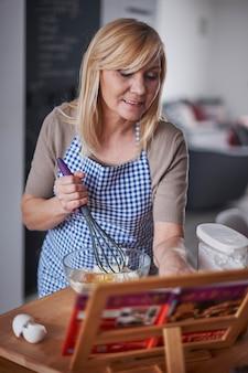 Blond kobieta trzepocze jajka i czyta przepis