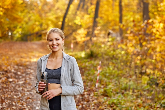 Blond kobieta trzyma butelkę wody w lesie, portret. pozytywna pani w stroju sportowym odpocznie po bieganiu, joggingu. w słoneczny jesienny dzień