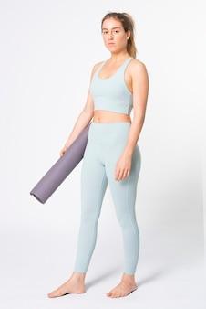 Blond kobieta trzyma matę do jogi w niebieskim sportowym biustonoszu i legginsach na całe ciało