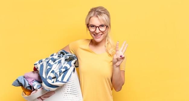 Blond kobieta uśmiecha się i wygląda przyjaźnie, pokazując numer trzy lub trzeci z ręką do przodu, odliczając w dół