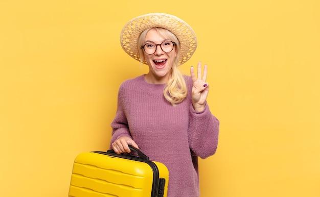 Blond kobieta uśmiecha się i wygląda przyjaźnie, pokazując numer trzy lub trzeci z ręką do przodu, odliczając