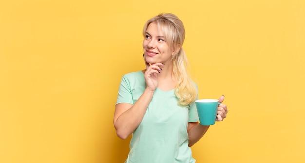 Blond kobieta uśmiecha się radośnie i marzy lub wątpi, patrząc w bok