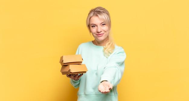 Blond kobieta uśmiecha się radośnie z przyjaznym, pewnym siebie, pozytywnym spojrzeniem, oferując i pokazując przedmiot lub koncepcję