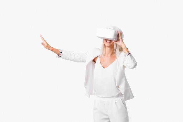 Blond kobieta w białym apartamencie z gogle wirtualnej rzeczywistości. album nagrywany na białej przestrzeni