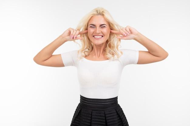 Blond kobieta w białym podkoszulku bez rękawów zamknęła oczy i uszy z powodu hałasu na białym czystym tle